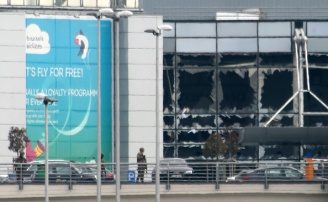 BRUSSELS, BELGIUM - MARCH 22: Crews and passengers being evacuated Zaventem Bruxelles International Airport after terrorist attcks. In the background glass front of departure hall appears to be blown out, on March 22, 2016 in Brussels, Belgium. (Photo by Sylvain Lefevre/Getty Images)
