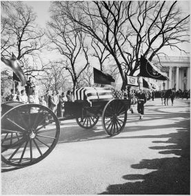 800px-Photograph_of_the_caisson_bearing_the_flag-draped_casket_of_President_John_F._Kennedy_leaving_the_White_House..._-_NARA_-_200455